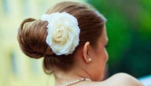 Прически на выпускной на длинные волосы, прическа с бубликом и украшением в виде цветка