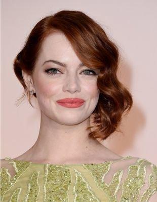 Рыжий цвет волос, прическа для круглого лица с уложенными на бок локонами